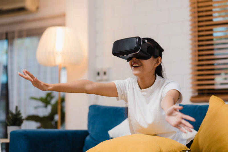 Asian teenager woman using glasses virtual reality simulator playing video games in living room, female feeling happy using relax time lying on sofa at home. Lifestyle women relax at home concept.