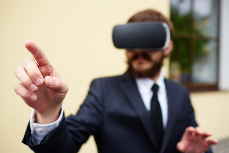 Businessman with augmented reality headset touching imaginary button to start vr game