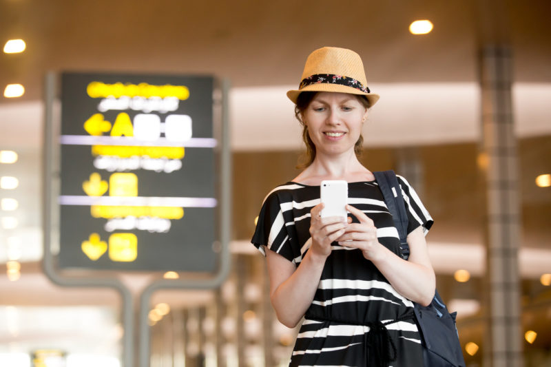 Smiling young woman in straw hat in her 20s walking in modern airport terminal building, holding smartphone, looking at screen, using cell phone app, typing or reading text message