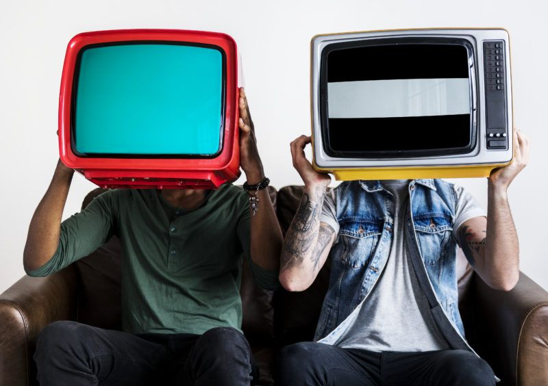 People holding retro television next to each other