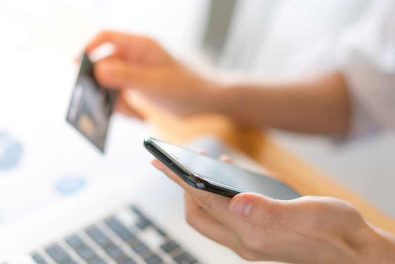 Hands holding a credit card using laptop computer and mobile phone for online shopping .