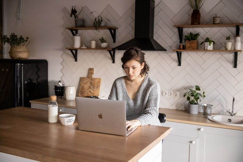 content-young-woman-browsing-laptop-in-modern-kitchen-4049793